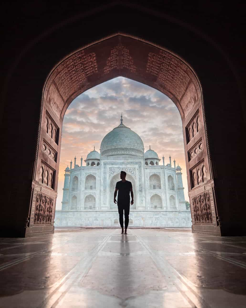 man_standing_in_archway_in_front_of_taj_mahal_agra_india